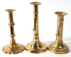 THREE EARLY BRASS PUSH-UP CANDLESTICKS